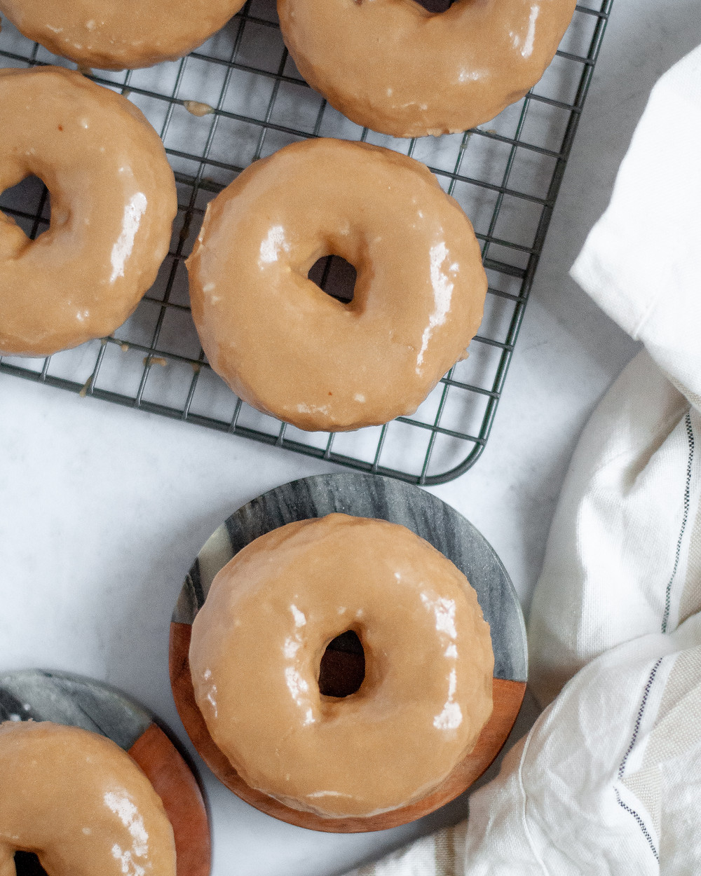 Top down view of baked maple donuts with maple glaze on a cooling rack.