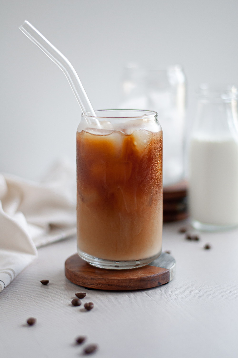 Icy glass of homemade cold brew coffee, served with milk and ready to drink with a straw