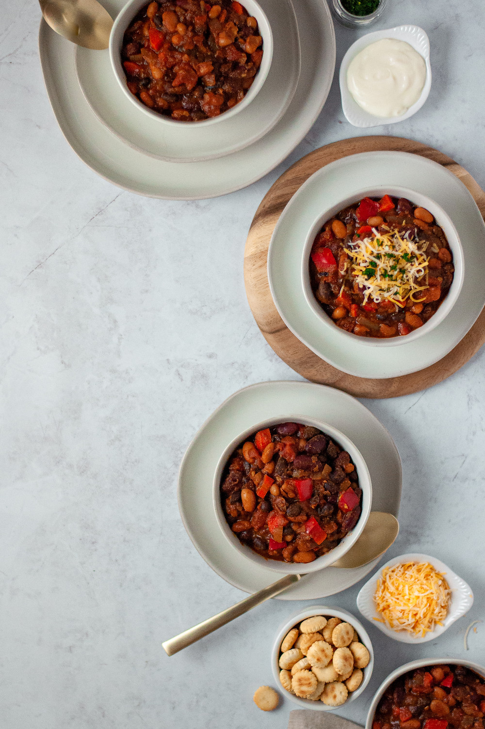 Top down view of 4 bowls of this veggie chili recipe, with a mixture of toppings both on the chili and in small bowls on the side