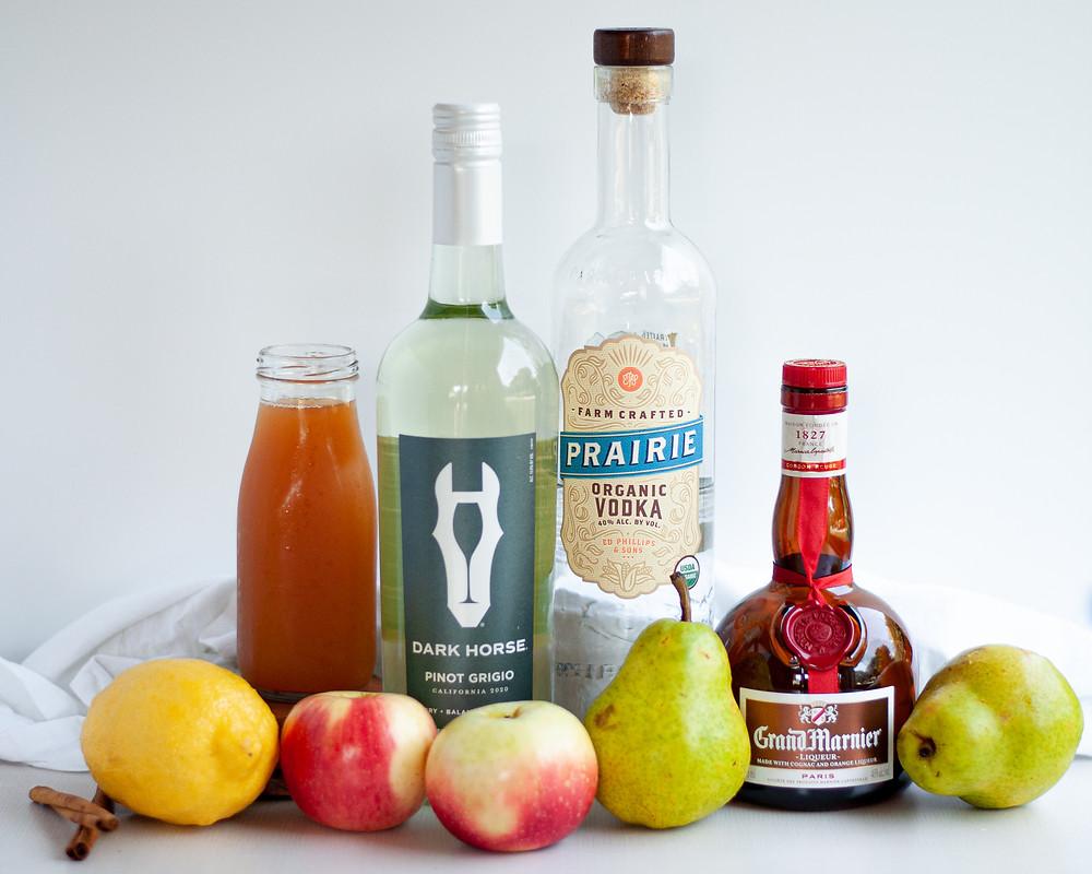 Ingredients to make fall apple pear sangria. Includes white wine, vodka, orange liqueur, apple cider, apples, pears, a lemon, and cinnamon sticks.