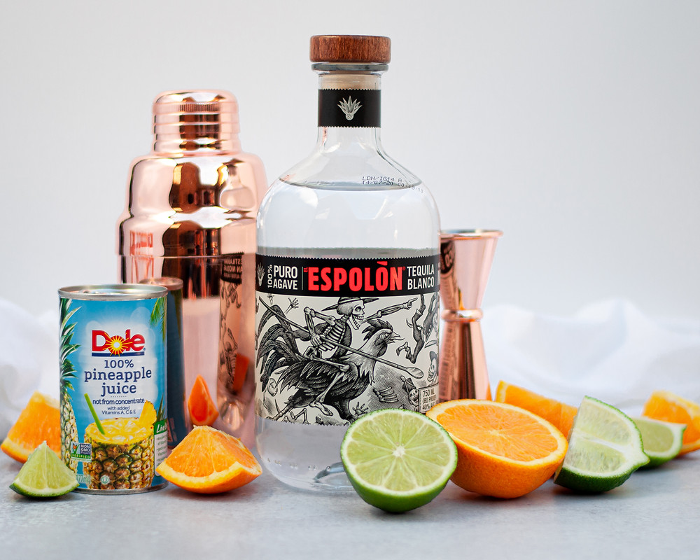 Ingredient shot for this skinny margarita recipe: orange slices, lime slices, pineapple juice and tequila.