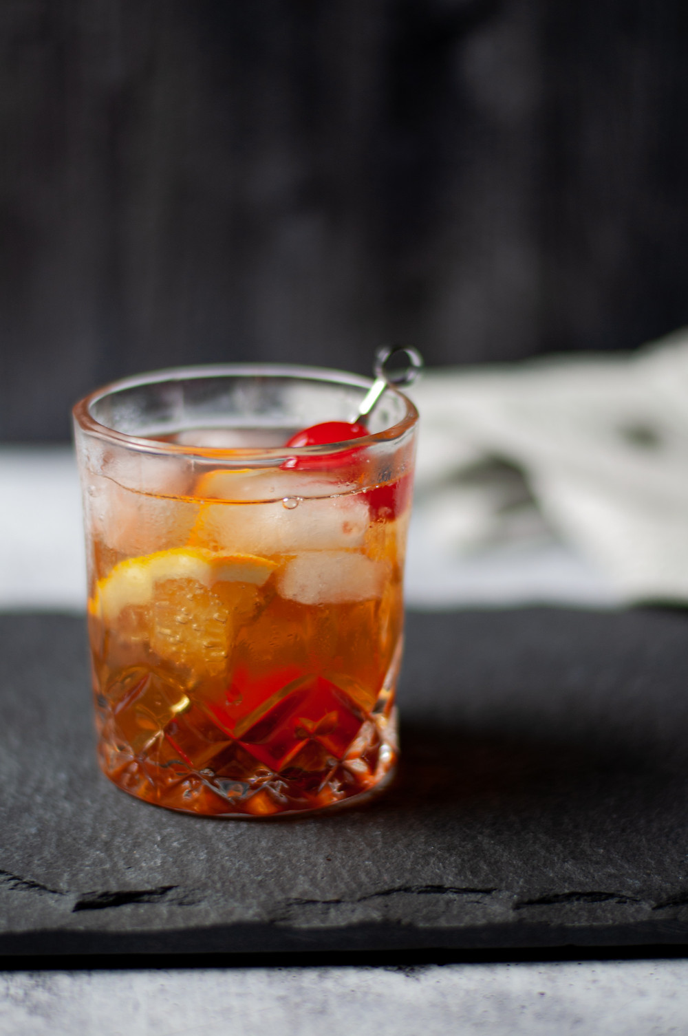 A single rocks glass of a brandy old fashioned sweet garnished with an orange wedge and maraschino cherry