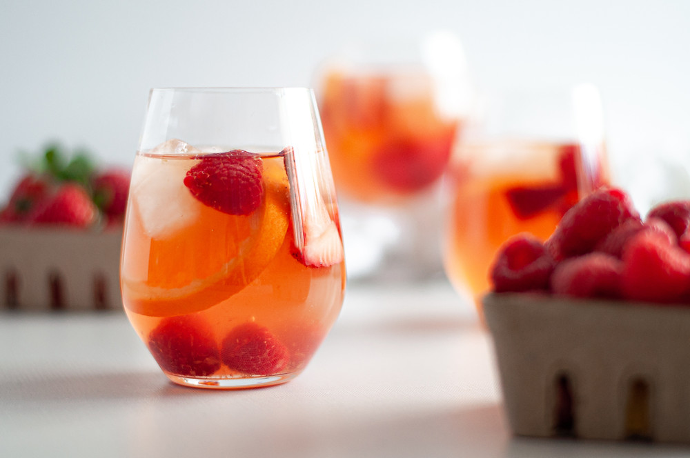 Straight on view of a stemless wine glass filled with rosé sangria, berries, orange slices, and ice. Surrounded by containers of berries and additional glasses filled with this rosé sangria recipe.