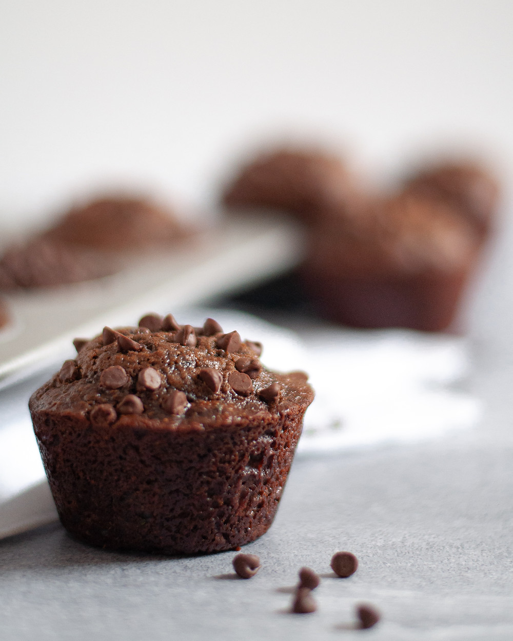 Close up of a chocolate zucchini muffin topped with mini chocolate chips, with additional chocolate zucchini muffins in faded in the background
