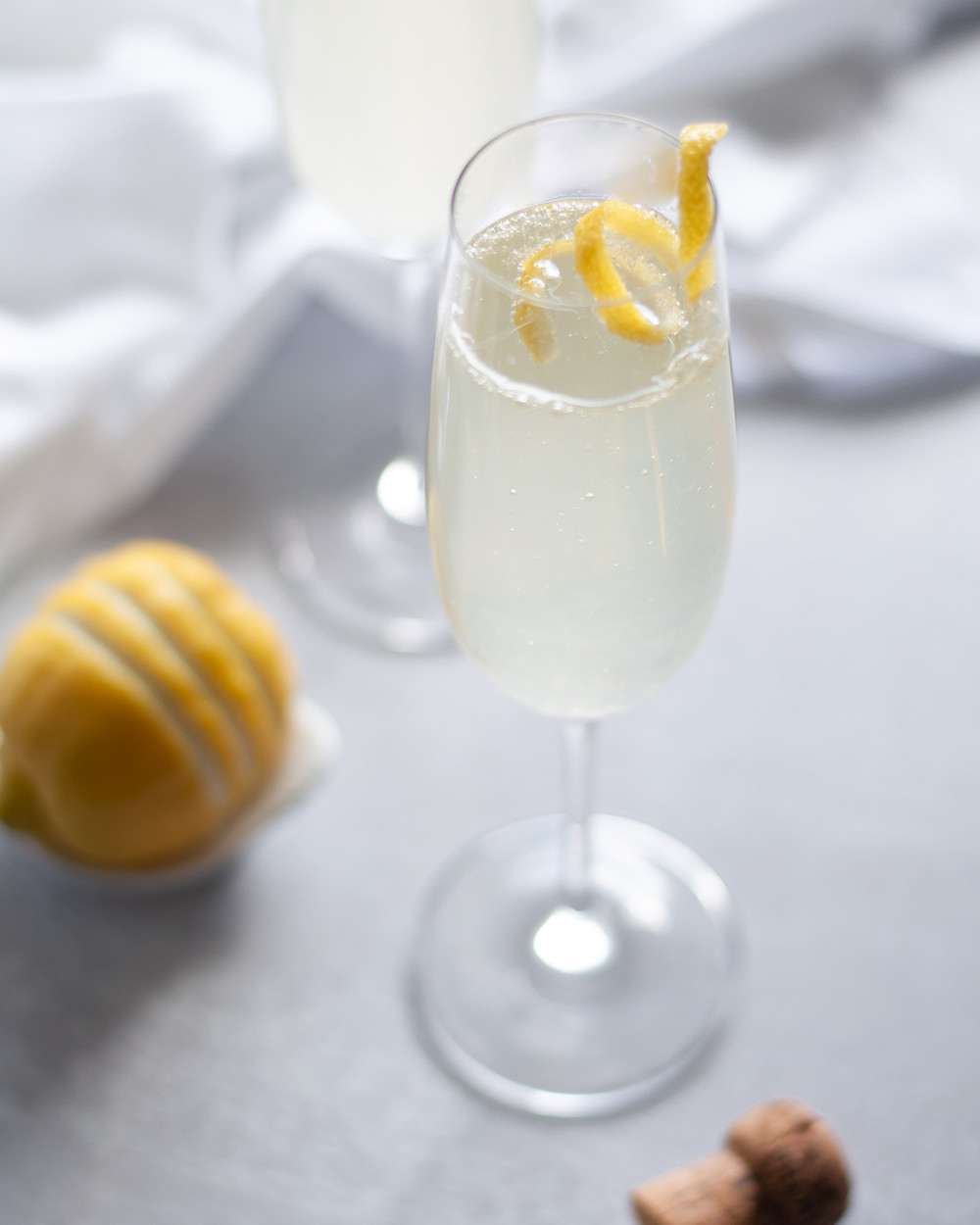 Champagne flute filled with this French 75 recipe and garnished with a lemon twist. Around the glass is a champagne cork, lemon, a 2nd cocktail, and a white napkin.