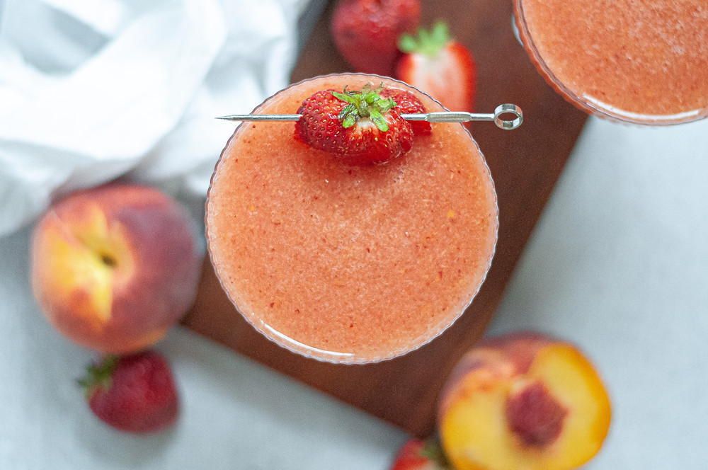 Top down image of a coupe glass filled with strawberry peach frose, garnished with a sliced strawberry on a cocktail stick. The glass is sitting on a wooden board, and is surrounded by strawberries, peaches, and a napkin.