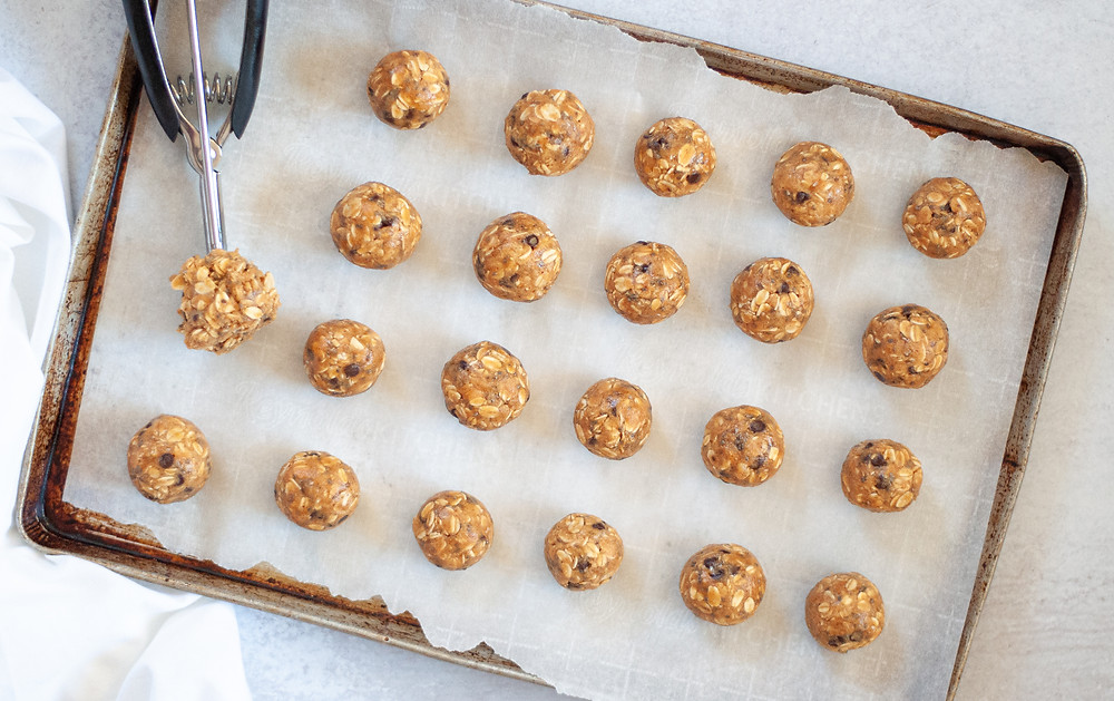 Top down view of a cookie sheet lined with parchment paper and filled with rolled protein balls and a cookie scoop filled with protein ball dough.