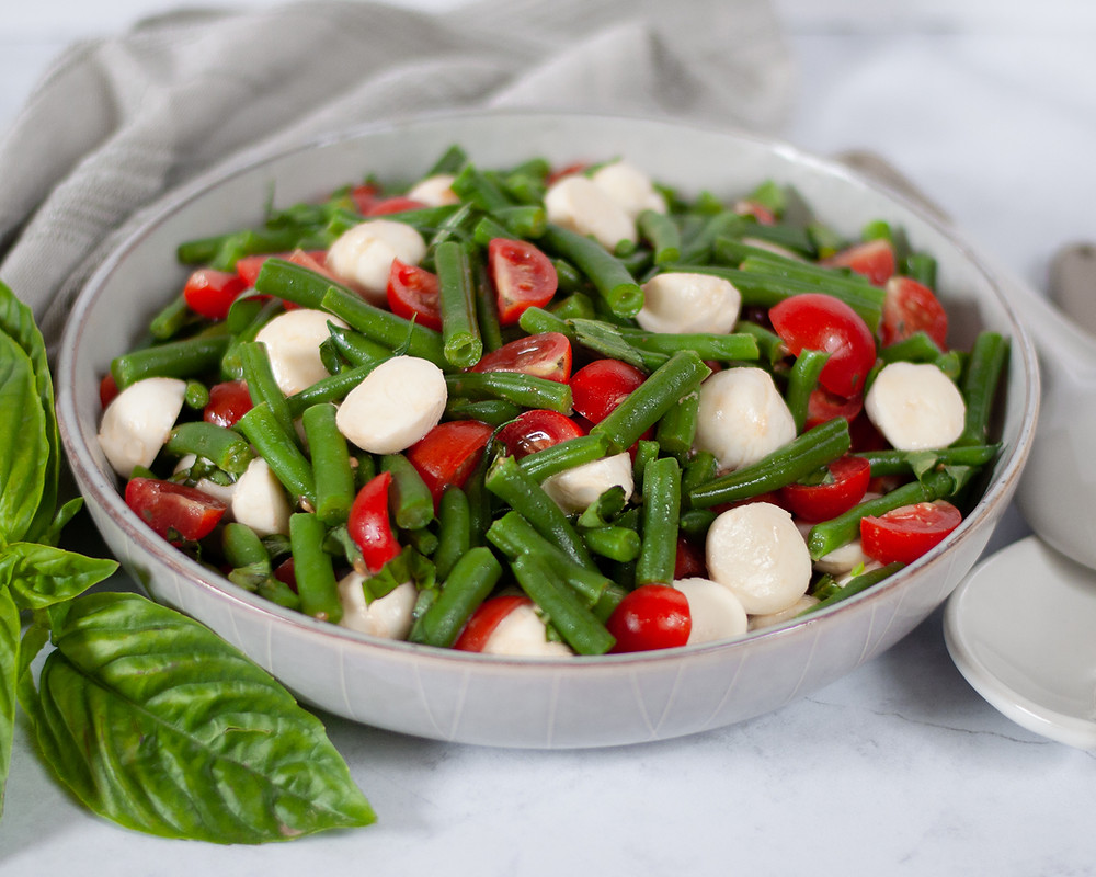 Large serving bowl filled with green bean caprese salad. The bowl is surrounded by basil, a cloth napkin, and serving spoons.