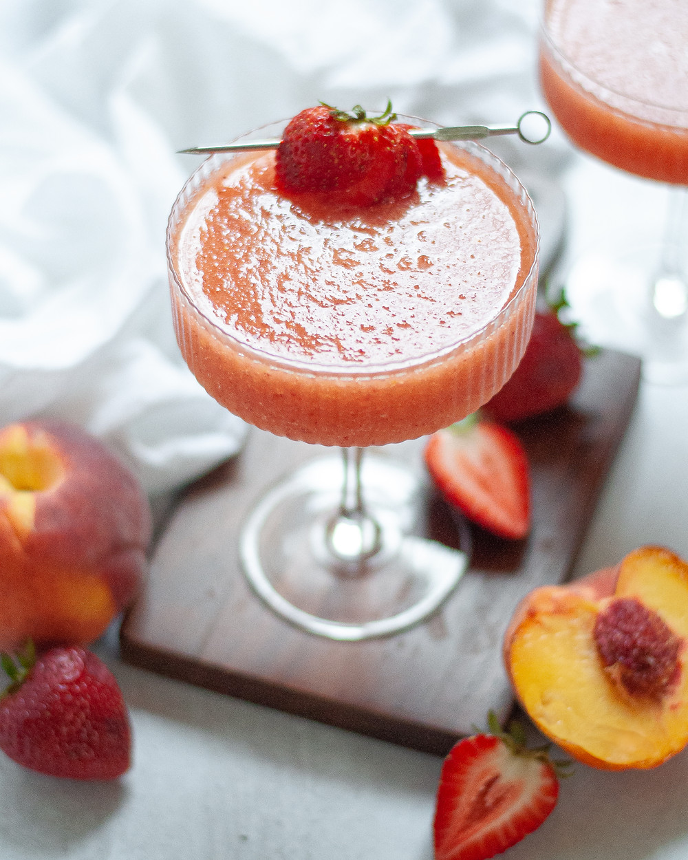 Coupe glass filled with this strawberry peach frose recipe. The glass is garnished with a sliced strawberry on a cocktail stick and it is sitting on a dark wooden board. The wine cocktail is surrounded by fresh fruit, a white napkin, and another cocktail is peaking into the top corner of the picture.