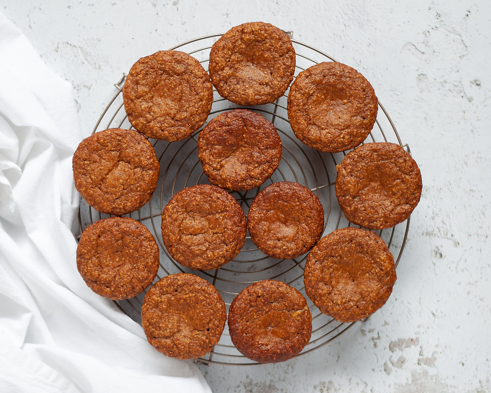 A circular cooling rack with 12 pumpkin protein muffins cooling on it. There is a white napkin next to the cooling rack.