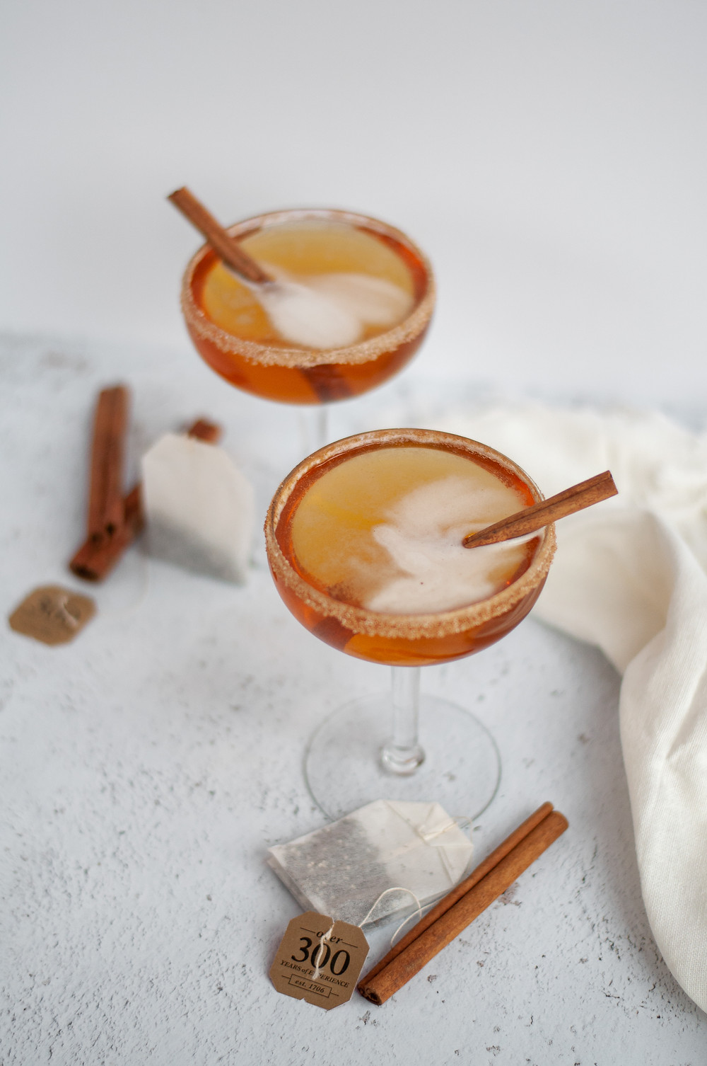 Another view of two coupe glasses filled with this bourbon cocktail recipe, garnished with cinnamon sticks and a cinnamon-sugar rim