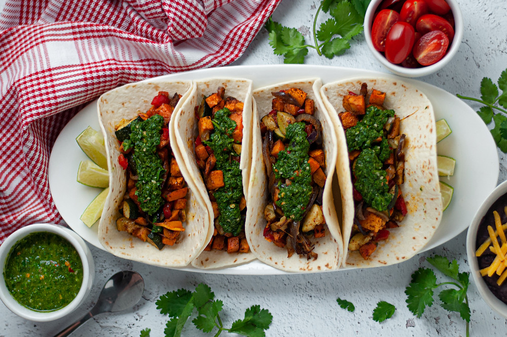 Top down view of a serving platter with 4 vegetarian tacos served up and ready to eat. Surrounded by a brightly colored napkin, tomatoes, cilantro, chimichurri sauce, and a side of beans