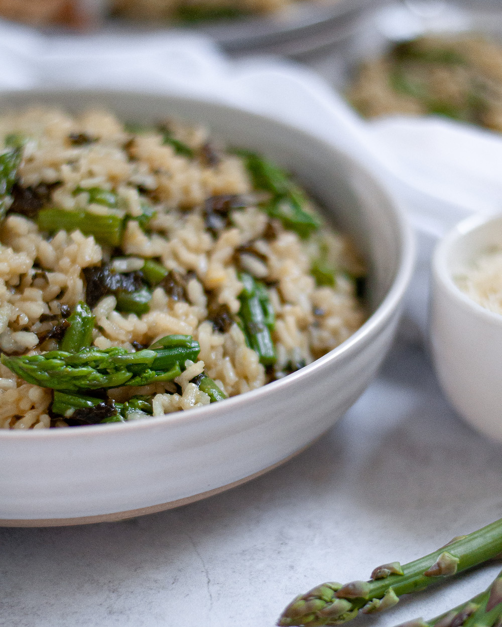 Close up of a serving bowl of this lemon risotto with asparagus and kale. There is fresh asparagus in the foreground, and a cup of grated parmesan and two plates with risotto on it in the background.