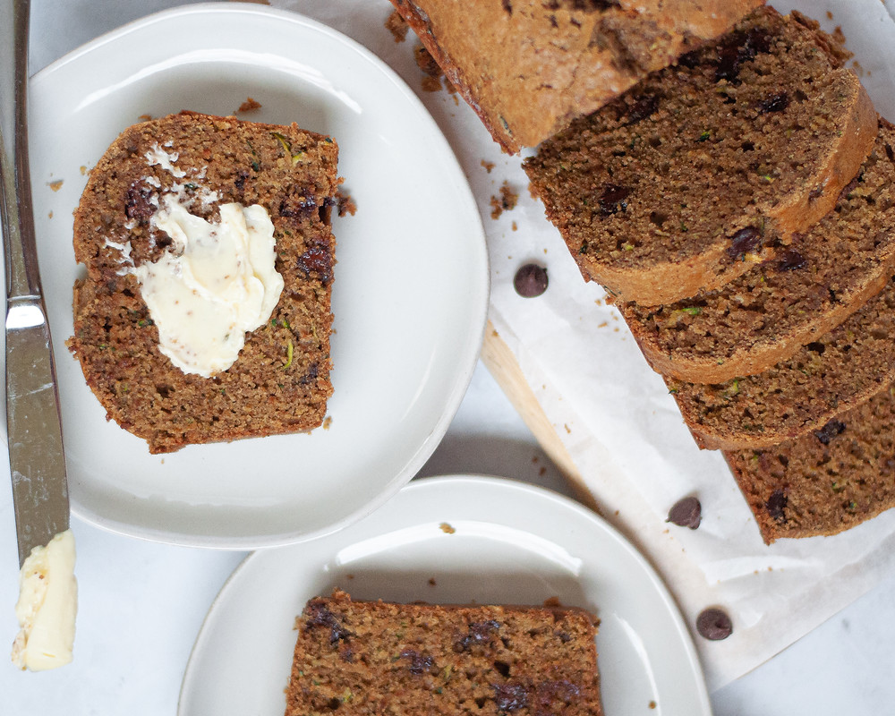 A loaf of healthy zucchini bread with chocolate chips sliced and sitting on a cutting board. There are also two plates with a slice of zucchini bread on each, one has a large smear of butter on it as well.