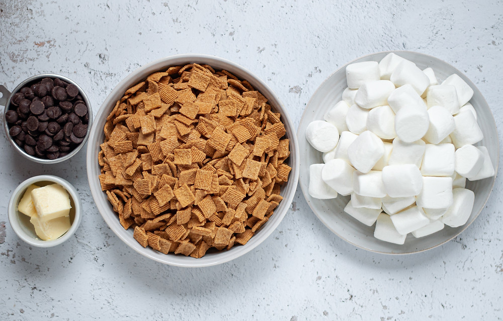 Ingredient shot for this cereal bars recipe. Includes a measuring cup filled with chocolate chips, 3 tablespoons of butter in a small bowl, a large bowl of graham cereal, and a large plate with jet-puffed marshmallows.