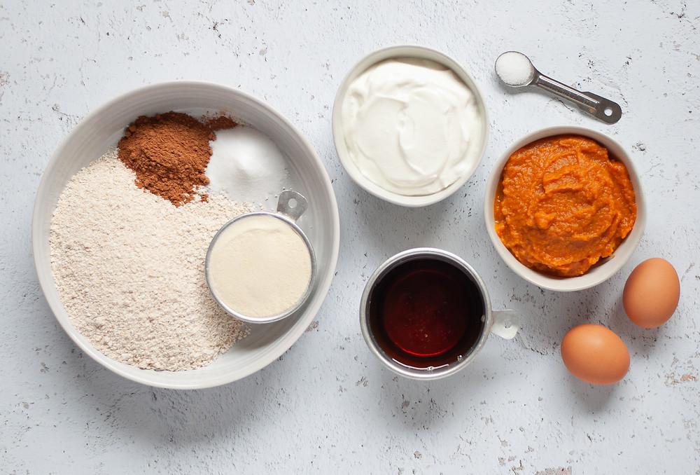 Ingredient shot to make these oat flour pumpkin muffins. This includes: oat flour, cinnamon, salt, baking soda, vanilla whey protein powder, plain greek yogurt, pure maple syrup, pumpkin puree, and eggs.
