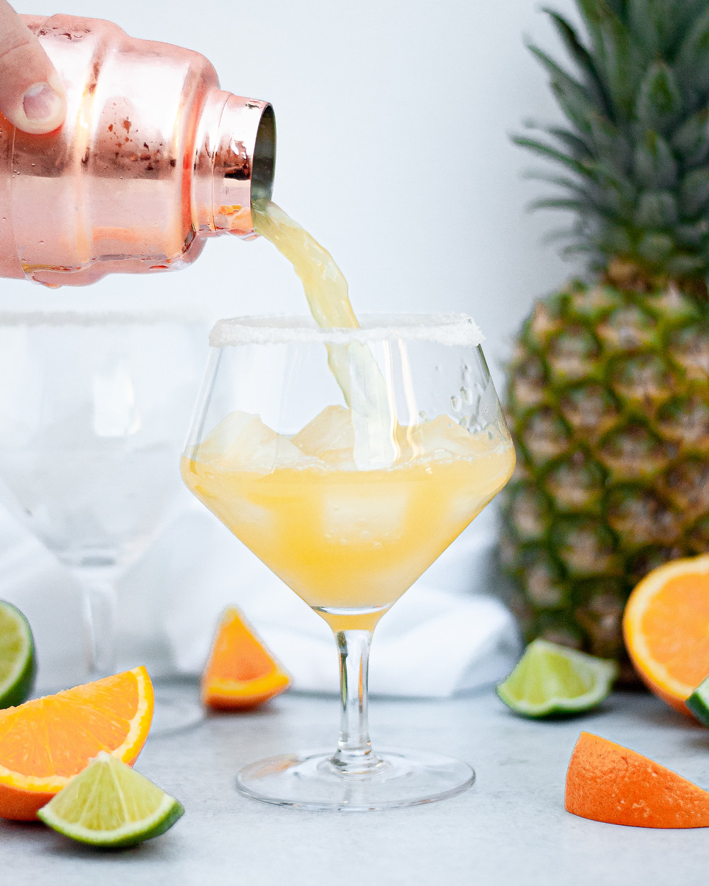 Pour shot of a glass being filled with a freshly shaken skinny pineapple margarita. Surrounded by slices or oranges and limes and a pineapple.