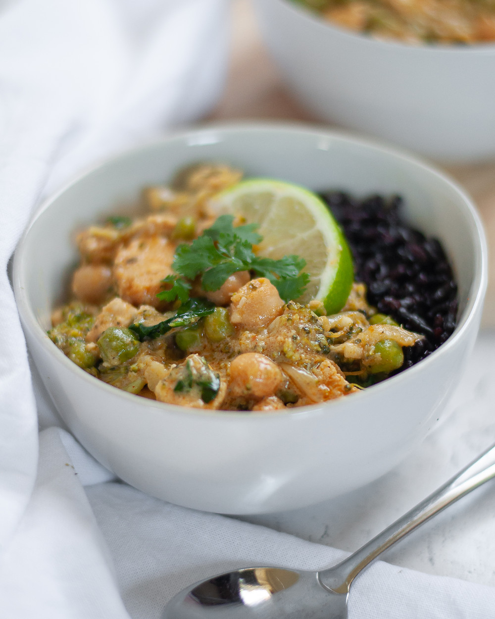 Close up shot of a bowl of chicken vegetable curry with chickpeas served with forbidden rice, a lime wedge, and cilantro.