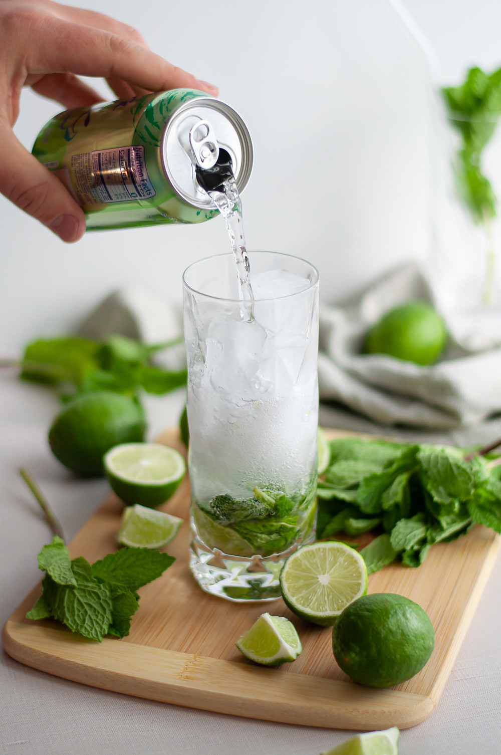 Image of the sparkling water being poured into the highball glass. The glass is on a cutting board and surrounded by lots of mint and limes.