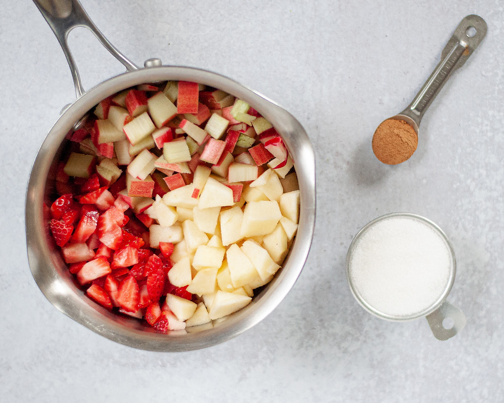 Saucepan filled with diced rhubarb, strawberries, and apples getting ready to make rhubarb compote. There is also a measuring cup with sugar and a measuring spoon with cinnamon.