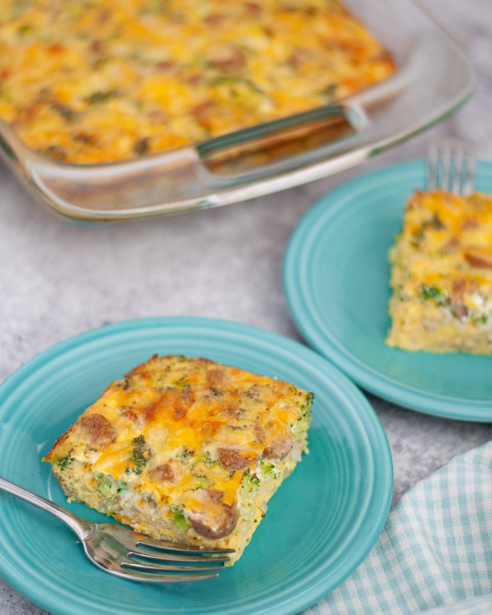 Another view of this easy breakfast casserole recipe, showing the pan next to two plates with slices of egg bake ready to eat