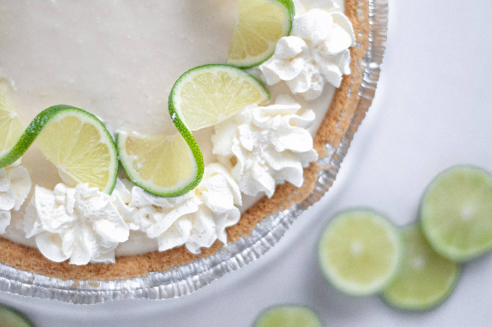 Top down view of this no bake key lime pie. The edge of the key lime pie is decorated with whipped cream and slices of lime.