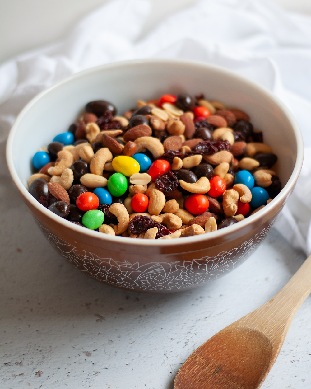 Bowl of homemade trail mix. The trail mix recipe pictured includes almonds, cashews, peanuts, peanut m&ms, dark chocolate covered almonds, and dried cherries.