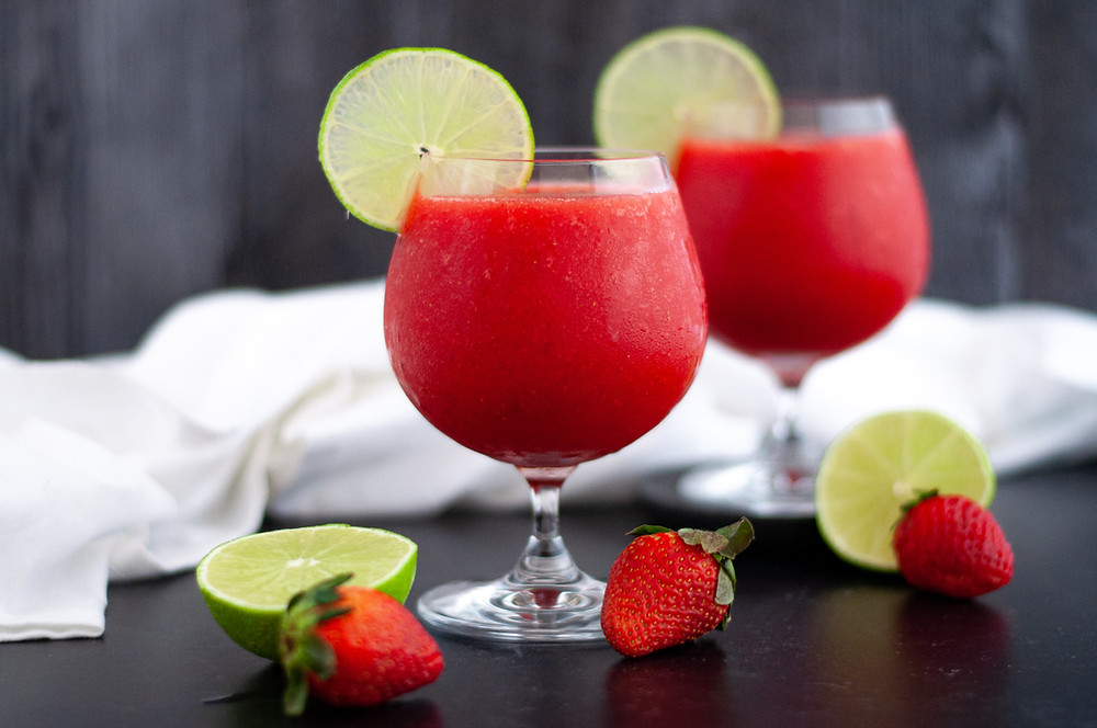 Two glasses of this Frozen Strawberry Daiquiri Recipe served with slices of lime