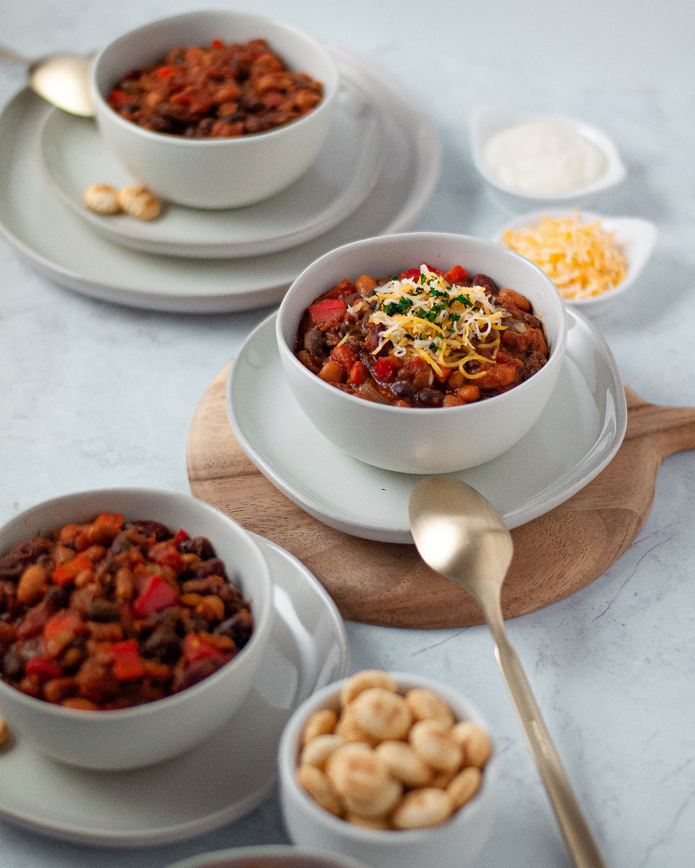 Three bowls filled with this vegetarian chili recipe topped with cheese and cilantro and a side of oyster crackers and sour cream