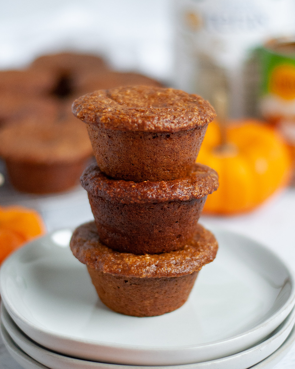 Close up of a stack of 3 healthy pumpkin muffins. There are additional oat flour muffins in the background, as well as mini pumpkins, a whey protein container, and a can of pumpkin puree.
