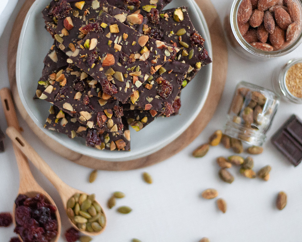 Top down view of a plate of dark chocolate bark with fruit and nuts, surrounded by the ingredients for chocolate bark: chocolate, ground flax, almonds, pistachios, pepitas, and cherries.