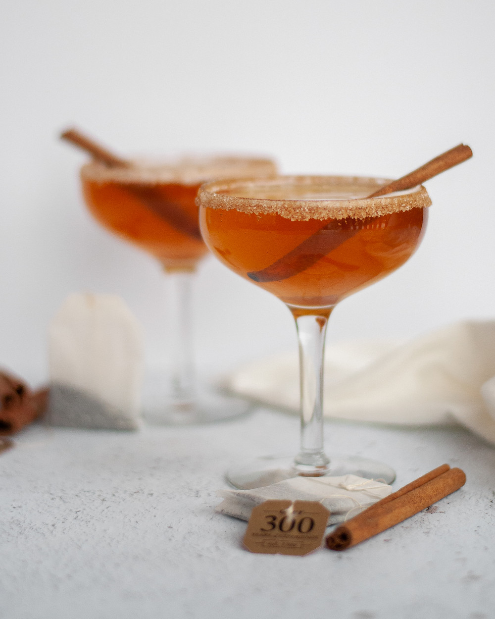 Two coupe glasses filled with this chai bourbon cocktail, garnished with cinnamon sticks and a cinnamon-sugar rim