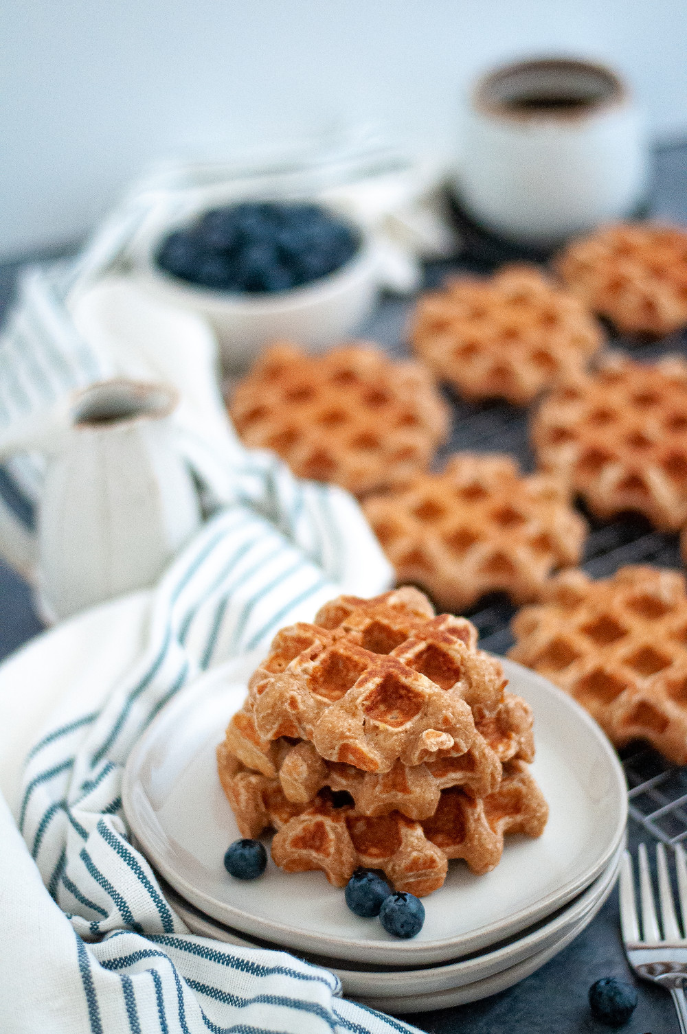 A stack of homemade waffles on a plate with additional whole wheat waffles on a cooling rack in the background