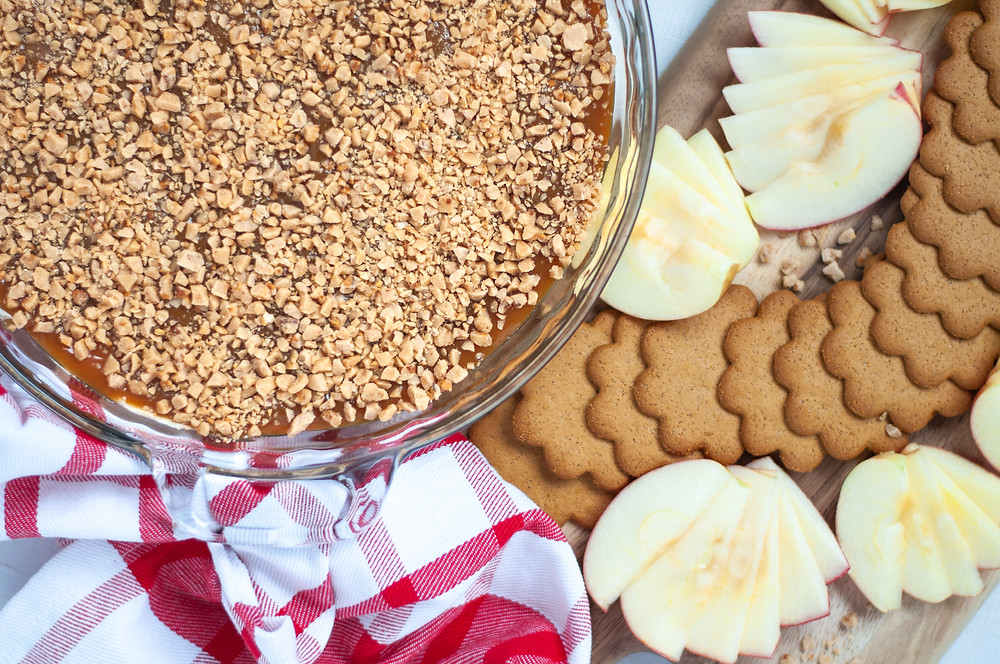 Top down view of a glass pie pan filled with this easy caramel apple dip. Next to a red and white checkered napkin and a tray of sliced apples and ginger snap cookies, ready to be dipped into this easy no bake dessert!