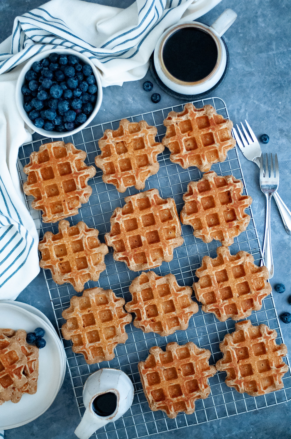 Top down view of this healthy waffle recipe displayed on a wire cooling rack with a carafe of maple syrup, bowl of blueberries, and a cup of coffee