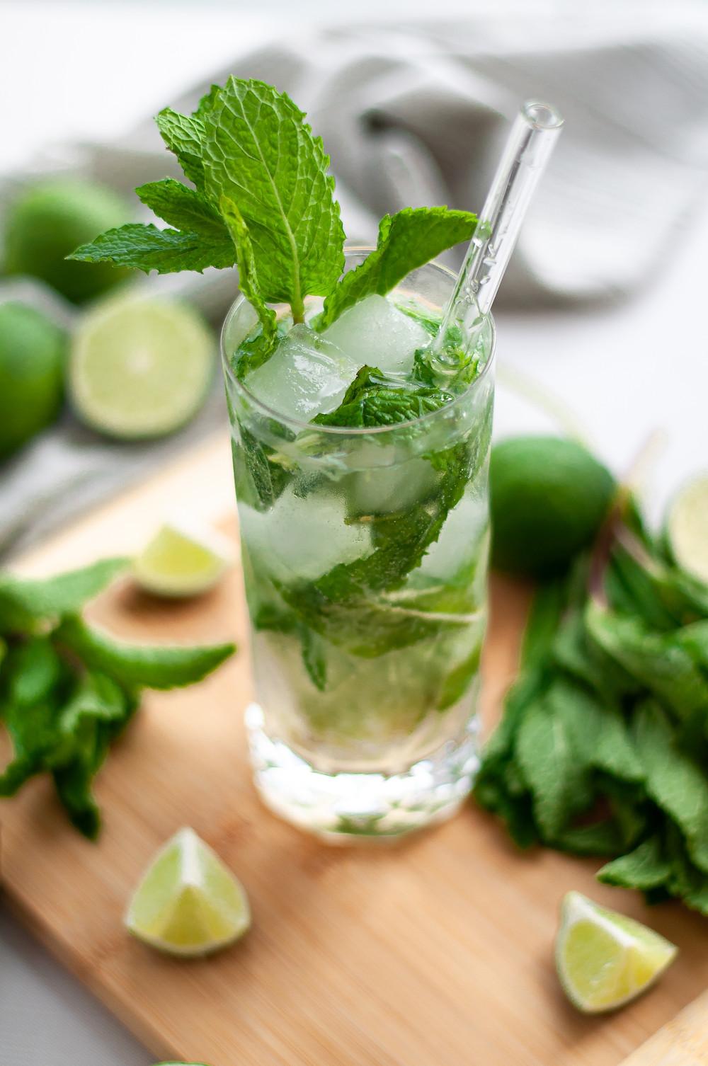 Highball glass filled with this mojito mocktail recipe. The glass has a sprig of mint for garnish and a straw, and is sitting on a cutting board covered in additional mint and lime wedges.