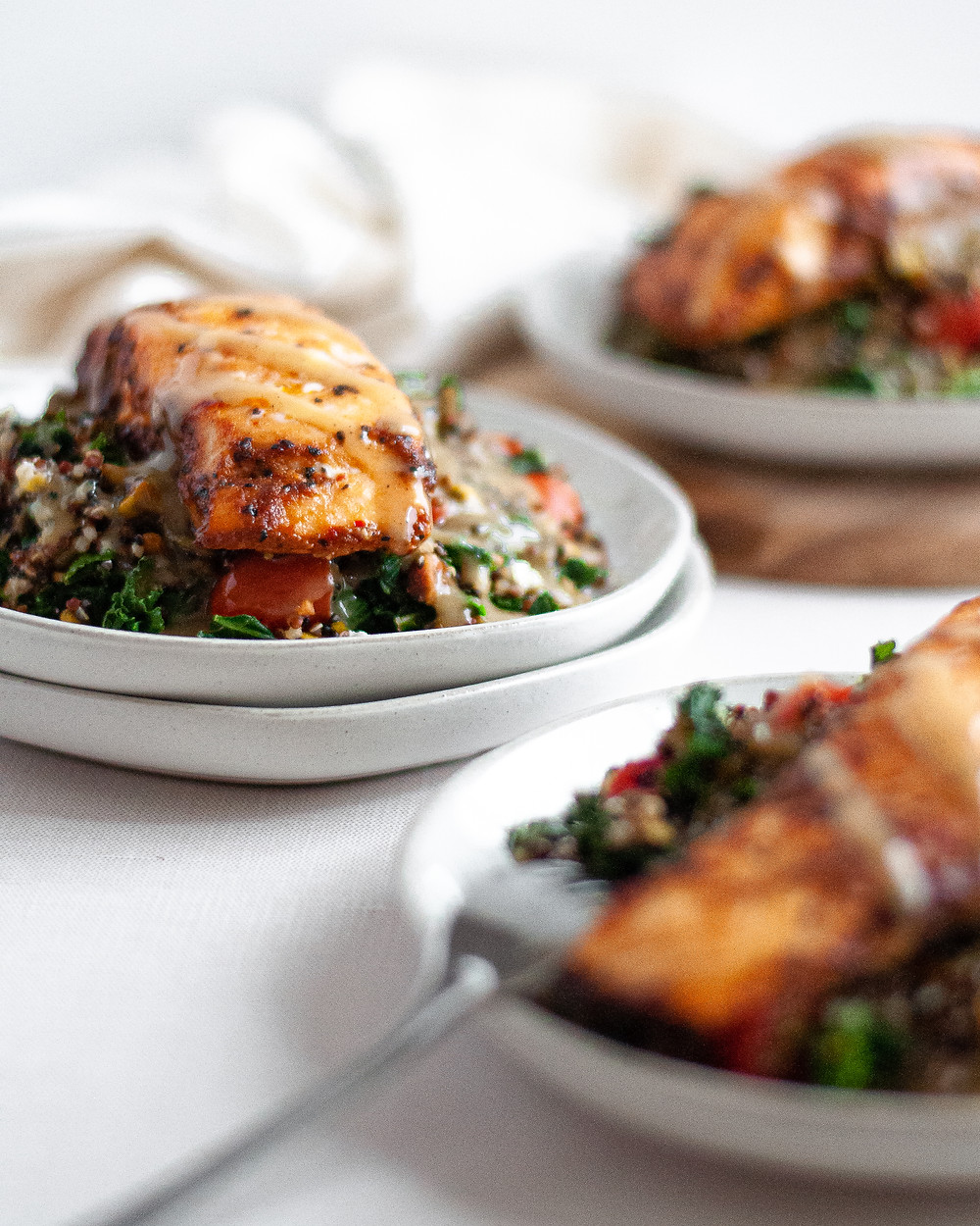 Three servings of kale and quinoa salad, topped with grilled salmon and homemade maple tahini dressing