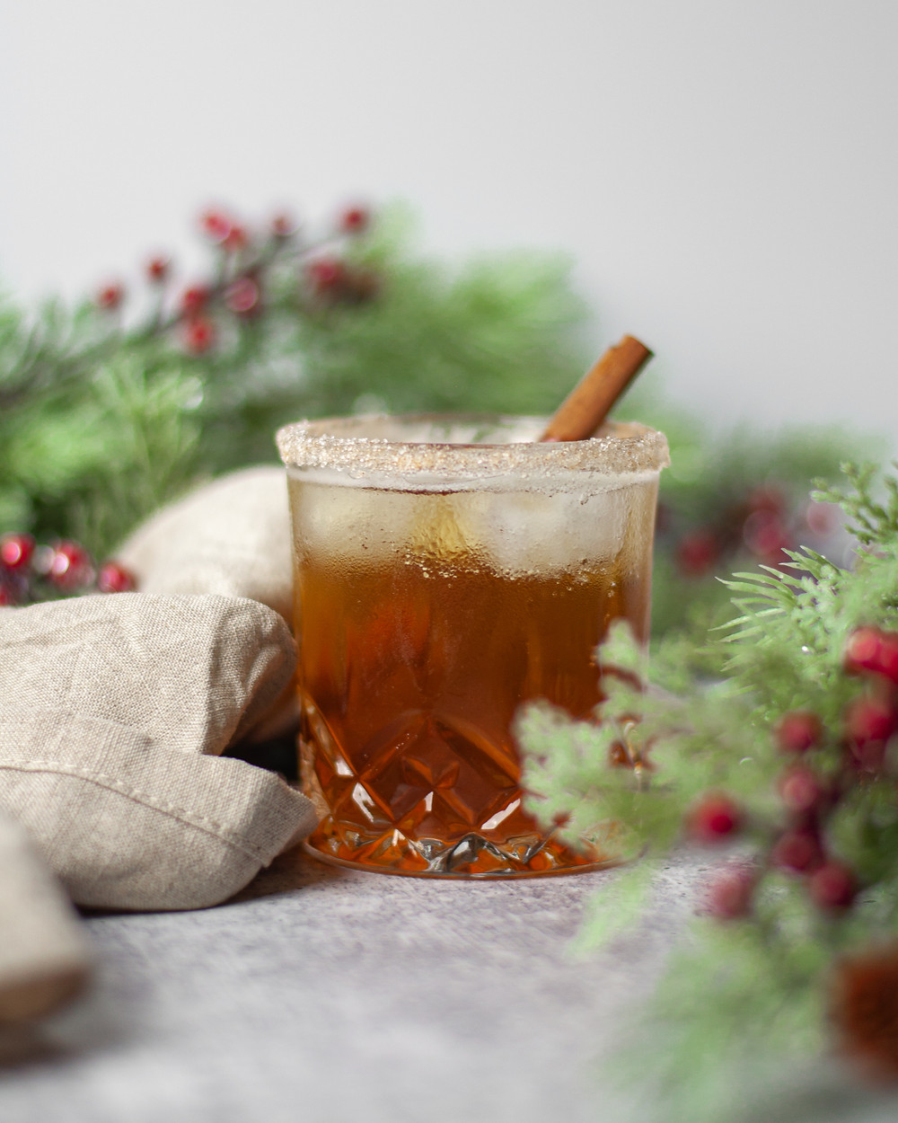 Christmasy scene showing one of our favorite winter bourbon drinks in a rocks glass garnished with a cinnamon stick and a cinnamon-sugar rim