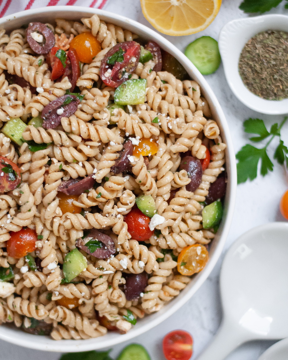 Close up, top down view of a serving bowl of Mediterranean pasta salad.