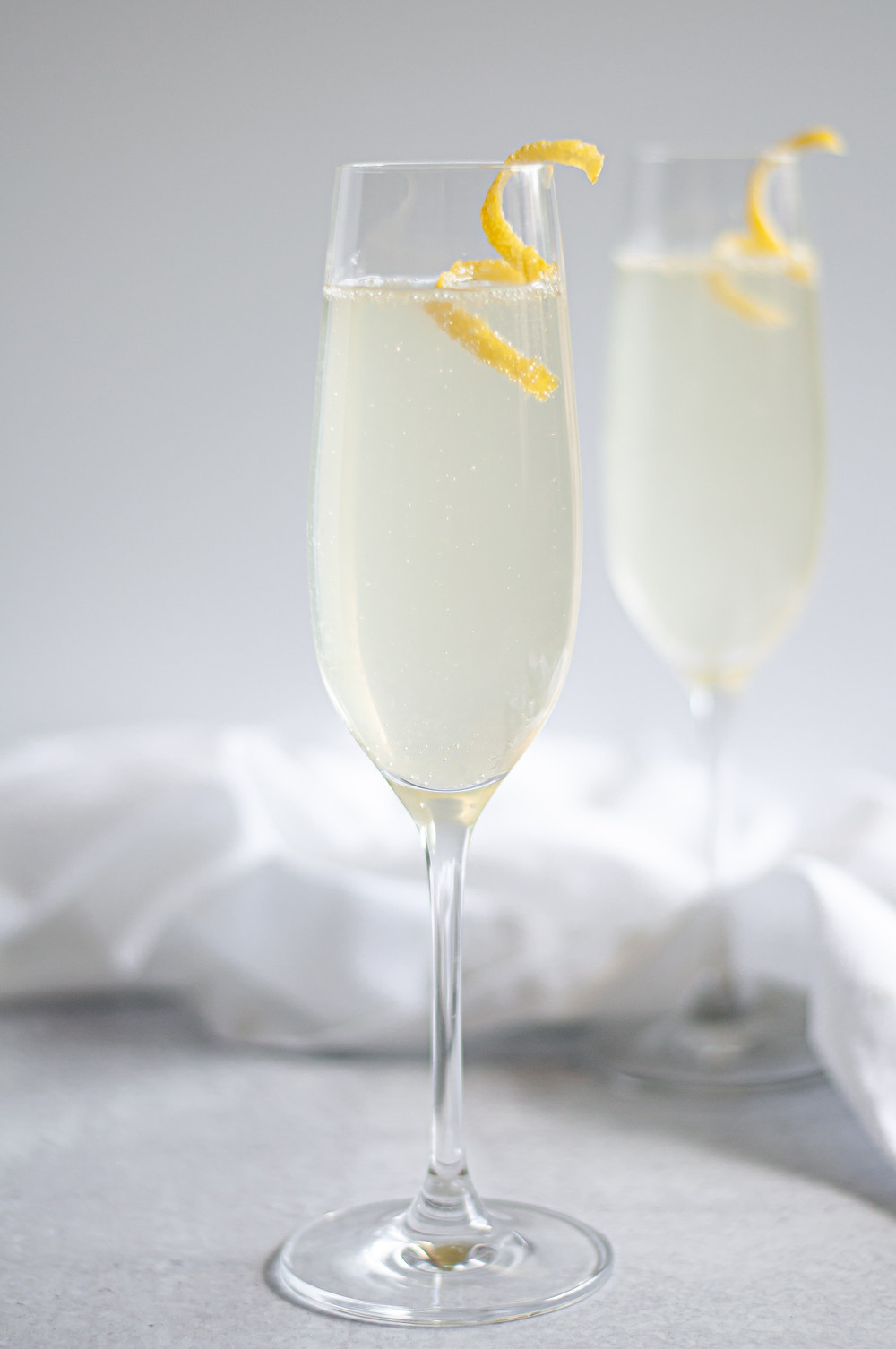 Two champagne flutes filled with this French 75 recipe and each is garnished with a lemon twist.