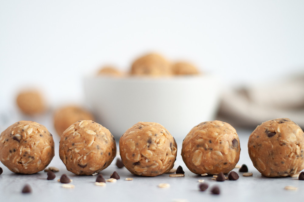 Line of peanut butter protein balls in the foreground, with a blurred out white bowl of energy bites in the background.