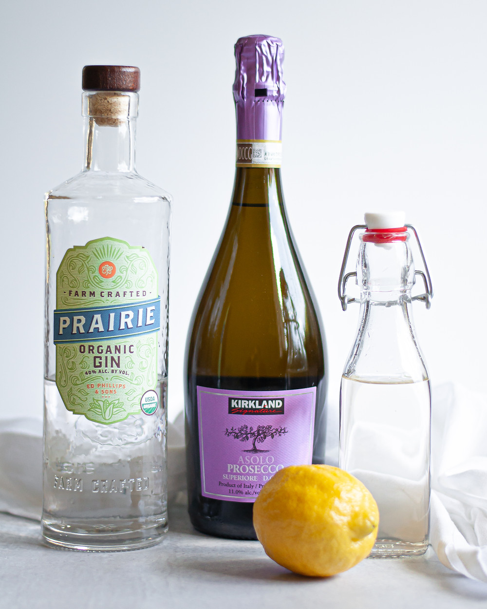 Ingredient shot for a Classic French 75 Cocktail. Includes: gin, champagne, simple syrup, and a lemon.