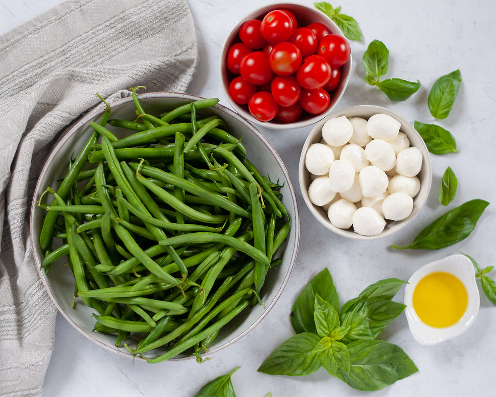 Top down view showing the ingredients needed for the summer side dish. There is a bowl of fresh green beans, cherry tomatoes, mozzarella balls, olive oil, and sprigs of basil.