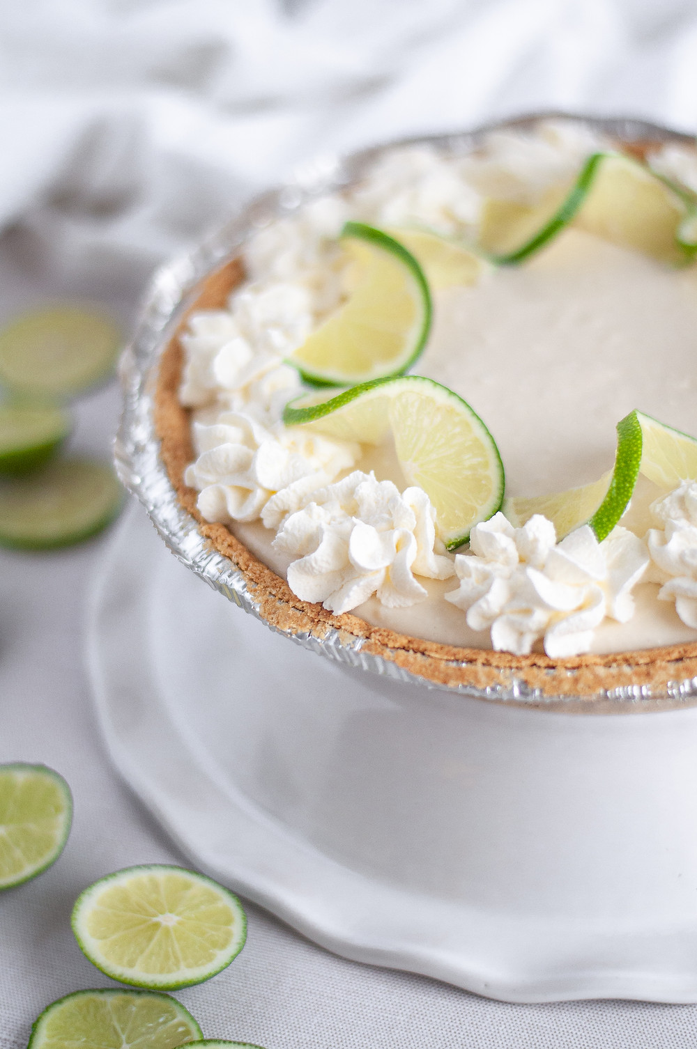 45-degree view of this easy key lime pie recipe made and sitting on top of a white ceramic pie plate. The no bake key lime pie is surrounded by additional lime slices and a white napkin.
