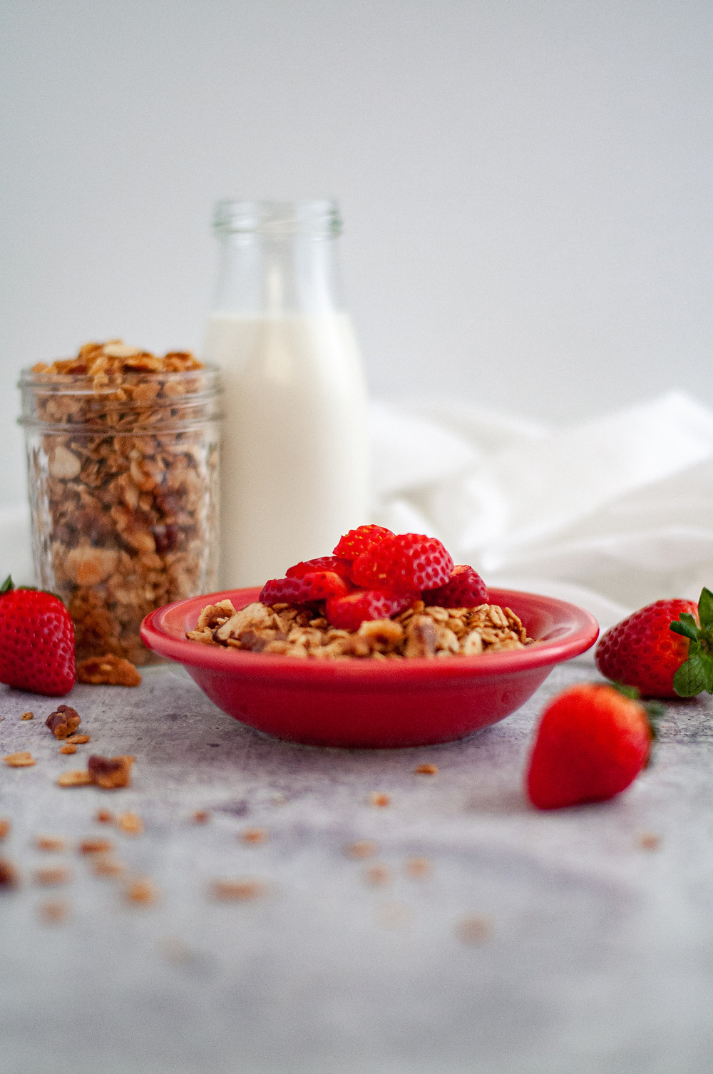Small red bowl of granola topped with slices of strawberries. This homemade granola is surrounded by strawberries, granola in a small glass jar as well as scattered around, and a glass jar of milk