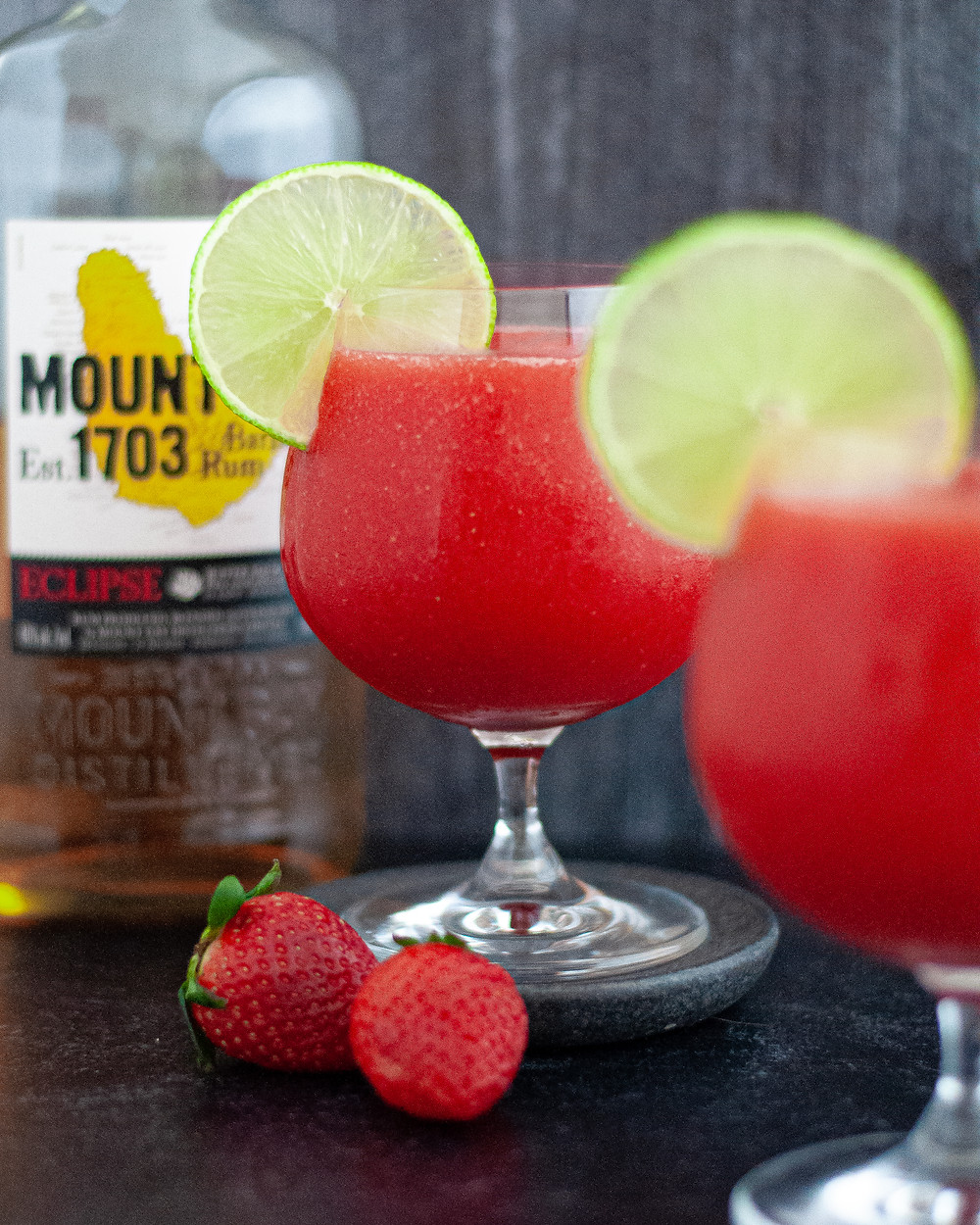 Two glasses of this Frozen Strawberry Daiquiri Recipe served with slices of lime, showcasing the daiquiri ingredients of rum, strawberries, and limes.