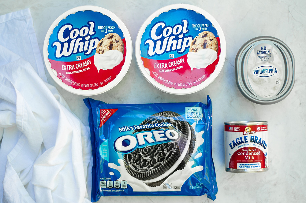 Top down view of the ingredients needed for this cookies and cream mousse recipe. This includes Cool Whip, Whipped Cream Cheese, Oreos, and Sweetened Condensed Milk.