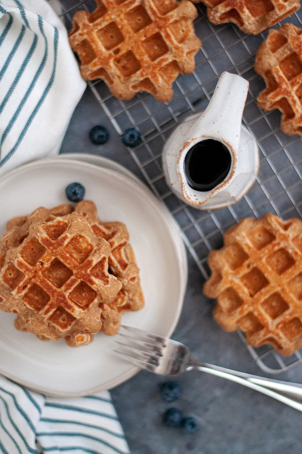 Top down view of a plate of waffles next to a pitcher of maple syrup