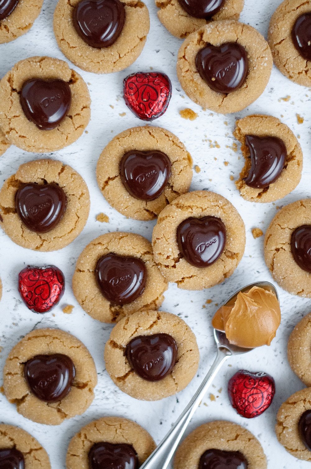 Top down view of these peanut butter blossom cookies with cookie crumbs, a spoonful of peanut butter, and extra heart-shaped chocolates