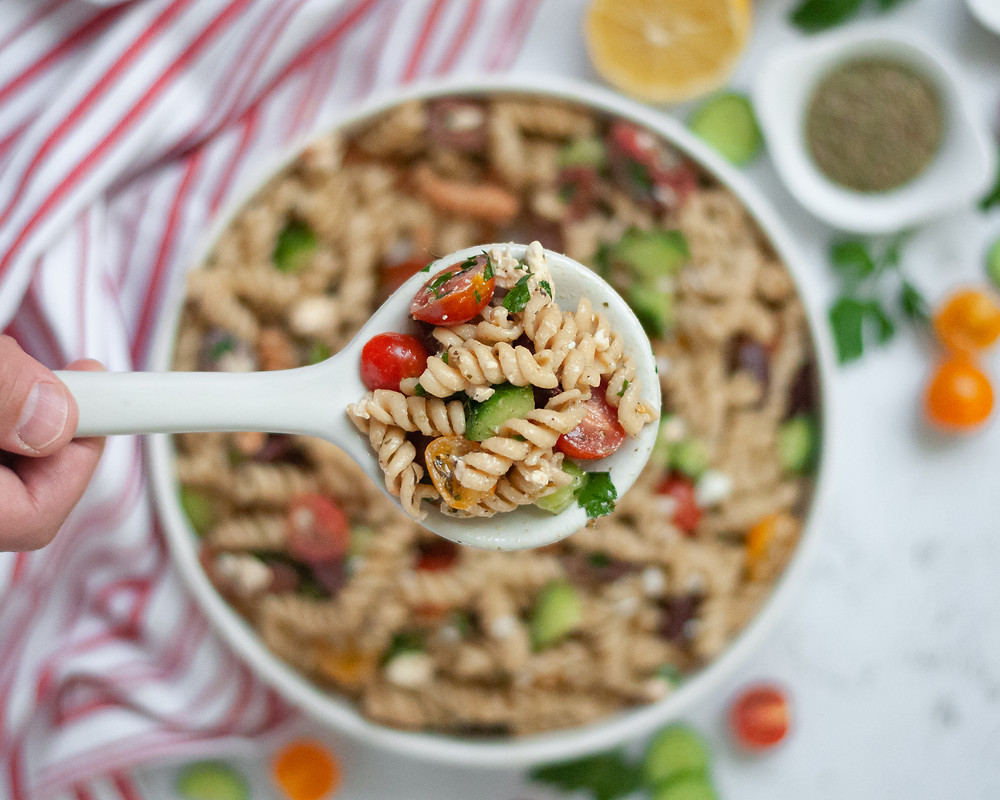 Top down view of a serving spoon filled with this vegetarian pasta salad held above a large bowl of Mediterranean pasta salad surrounded by ingredients and a striped napkin.